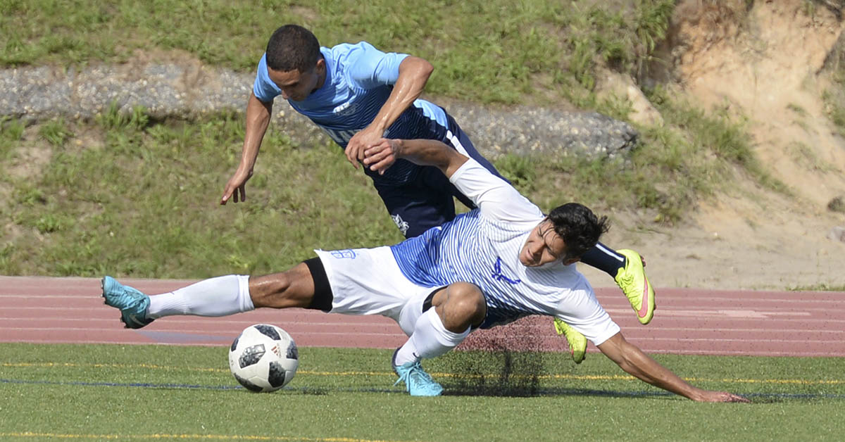 Air Force Capt. Aaron Zendejas (bottom), stationed at Tinker Air Force Base, Okla., battles for ball possession against Navy defenseman PO3 Orlando Zapatagarcia (top), stationed at Naval Air Station Lemoore, Calif., during the 2018 Armed Forces MenÕs Soccer Championship at Fort Bragg. (MC2 John Benson/Navy)