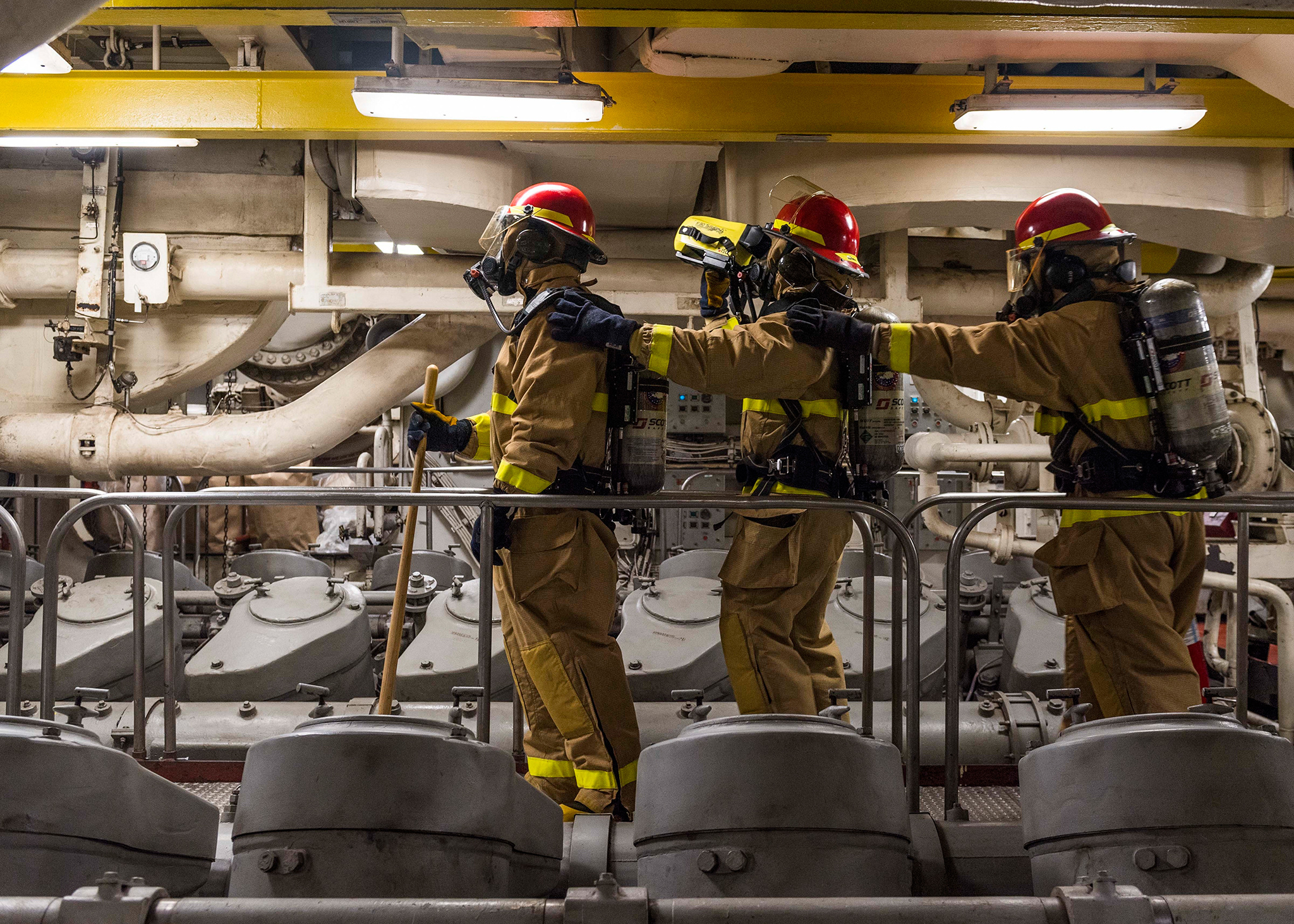 Sailors simulate overhauling a space using a Naval Firefighting Thermal Imager on Feb. 13, 2019, during a main space fire drill in the Main Machinery Room (MMR) 2 of the amphibious dock landing ship USS Ashland (LSD 48) in the South China Sea. (Mass Communication Specialist 2nd Class Markus Castaneda/Navy)