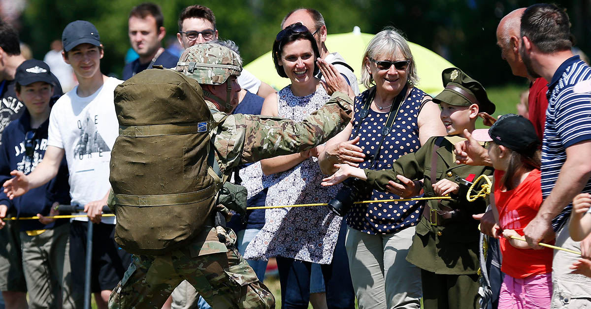 A US soldier claps in the hand of a child wearing a military uniform who attends the 74th anniversary of the D-Day ceremony, commemorating the World War II Allied landing in Normandy in Sainte-Mere-Eglise, northwestern France on June 3, 2018. - (CHARLY TRIBALLEAU/AFP/Getty Images)