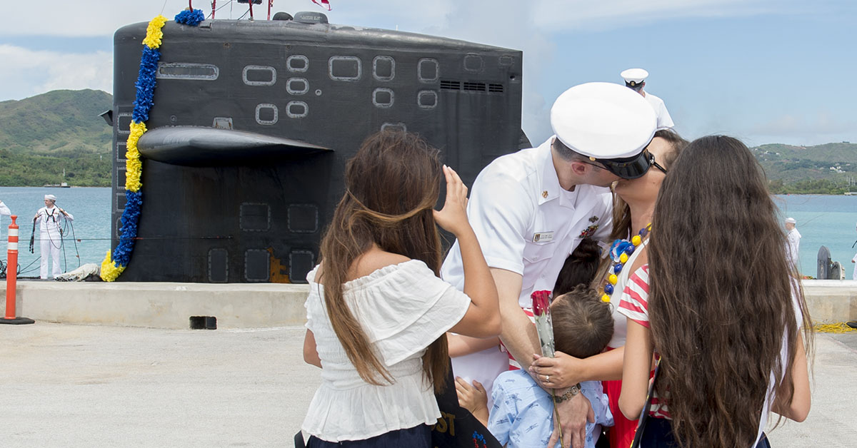 Chief Electronics Technician Navigation Michael Levy receives a kiss from wife Crystal during a homecoming ceremony on the pier for Los-Angeles class fast attack submarine USS Oklahoma City (SSN 723), June 29. Oklahoma City is one of four forward-deployed submarines assigned to Commander, Submarine Squadron 15. (Culinary Specialist Seaman Jonathan Perez/Navy)