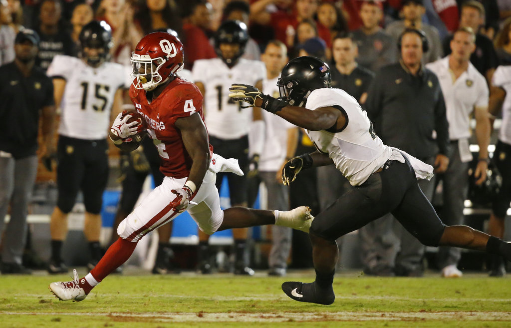 Oklahoma running back Trey Sermon (4) carries past Army defensive back James Gibson, right, in overtime of an NCAA college football game in Norman, Okla., Saturday, Sept. 22, 2018. Oklahoma won 28-21 in overtime. (Sue Ogrocki/AP)