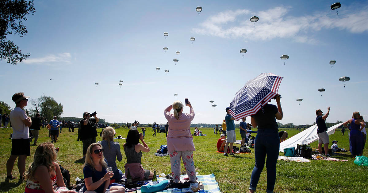 People look at US soldiers landing with their parachutes during the 74th anniversary of the D-Day ceremony, commemorating the World War II Allied landing in Normandy in Sainte-Mere-Eglise, northwestern France on June 3, 2018. - The D-Day anniversary is celebrated on June 2 and June 3, 2018 instead of its real day June 6. (CHARLY TRIBALLEAU/AFP/Getty Images)