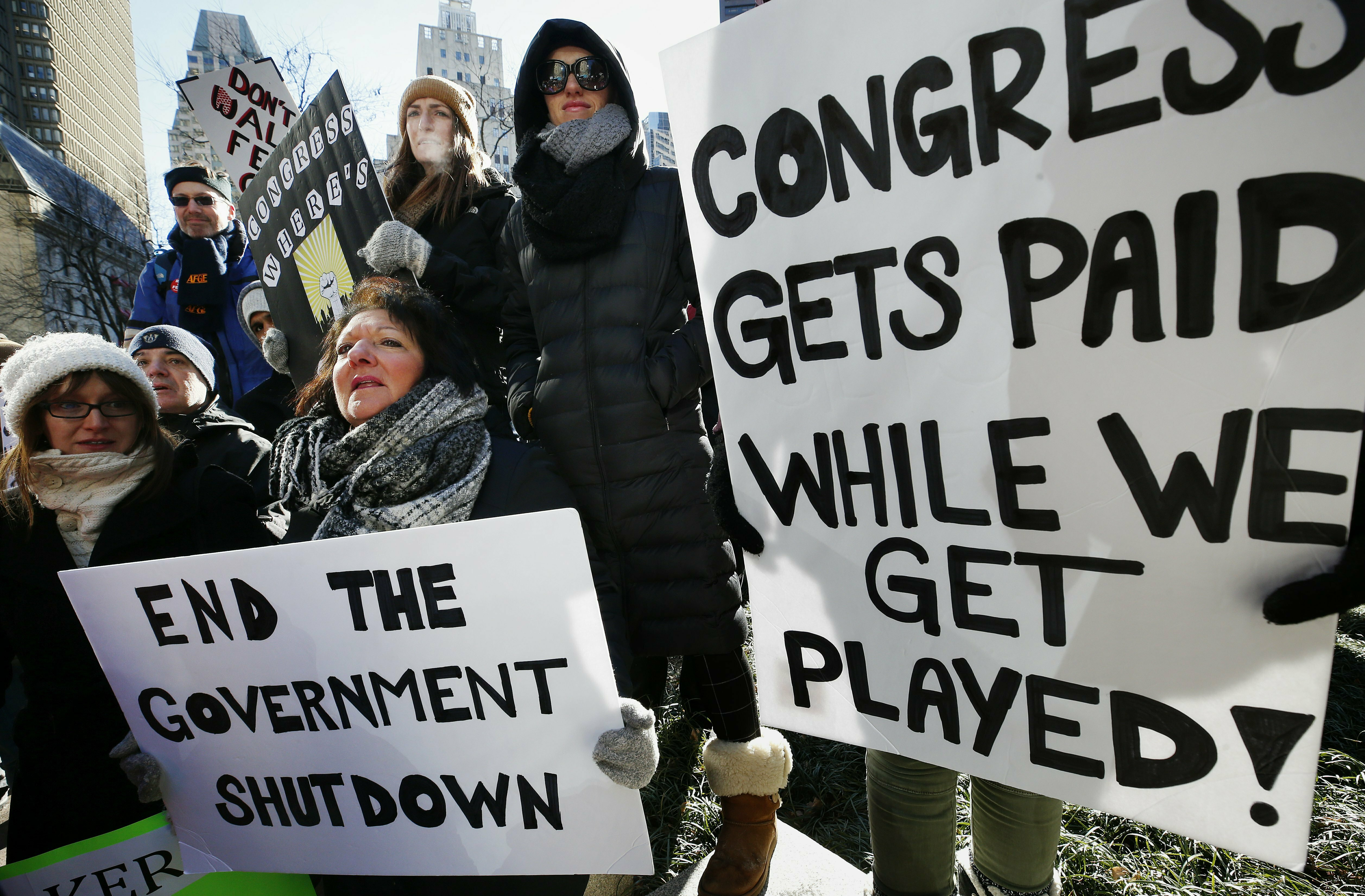 Government workers and their supporters hold signs during a protest in Boston on Jan.11, 2019. On Tuesday, national veterans groups implored lawmakers to find a solution to the ongoing budget impasse. (Michael Dwyer/AP)