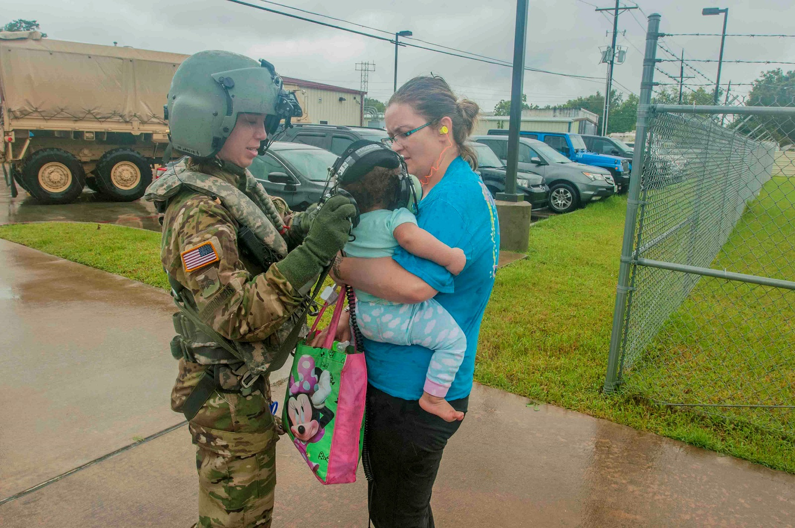 Sgt. Sara Cashdollar, an Army Reserve flight paramedic with C Company, 7-158 General Services Aviation Battalion, escorts a mother and her child off an aeromedical evacuation helicopter in Conroe, Texas, August 29, 2017. (Capt. Loyal Auterson/Army)