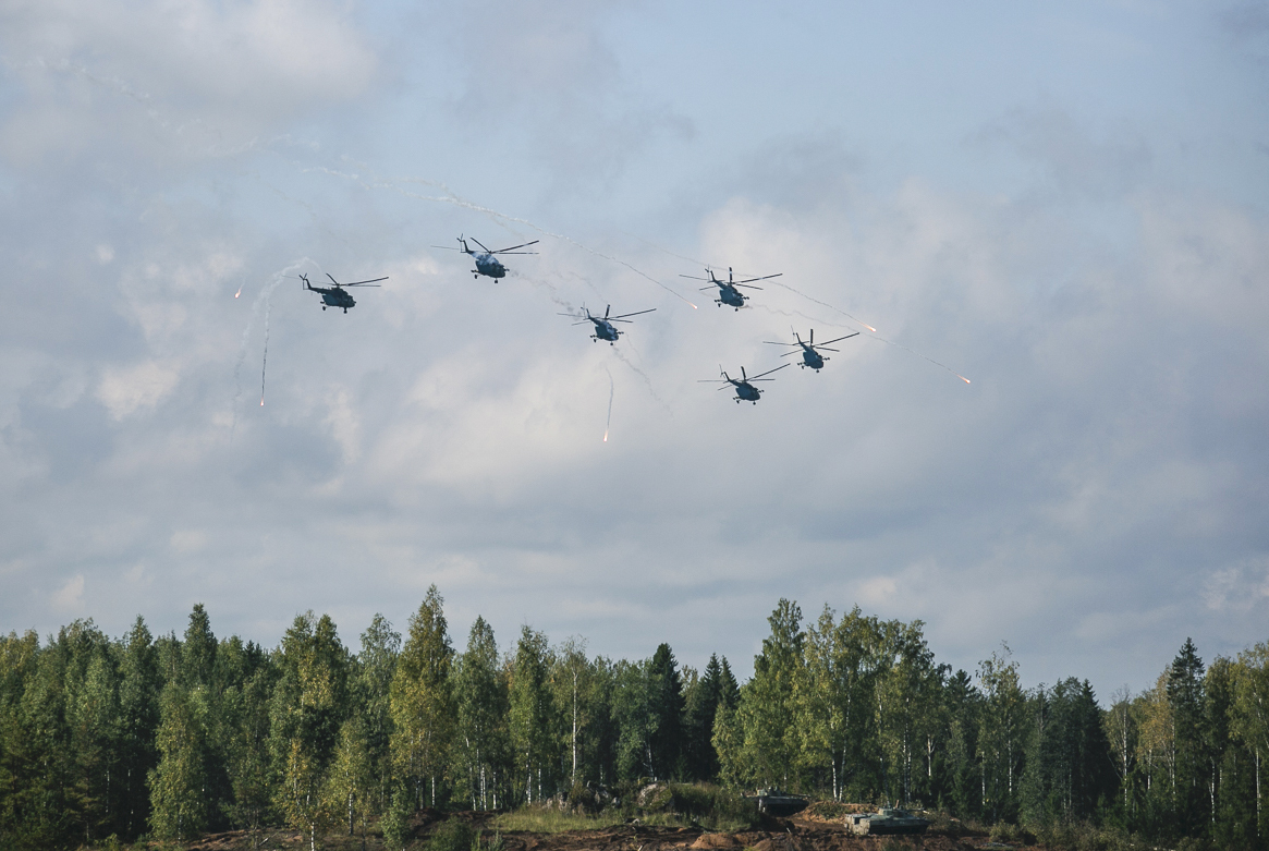 Russian military helicopters fly during a military exercise at a training ground at the Luzhsky Range, near St. Petersburg, Russia, on Sept. 18, 2017. The Zapad 2017 maneuvers have caused concern among some NATO members neighboring Russia, who have criticized a lack of transparency about the exercises and questioned Moscow's real intentions. (Russian Defence Ministry Press Service via AP)