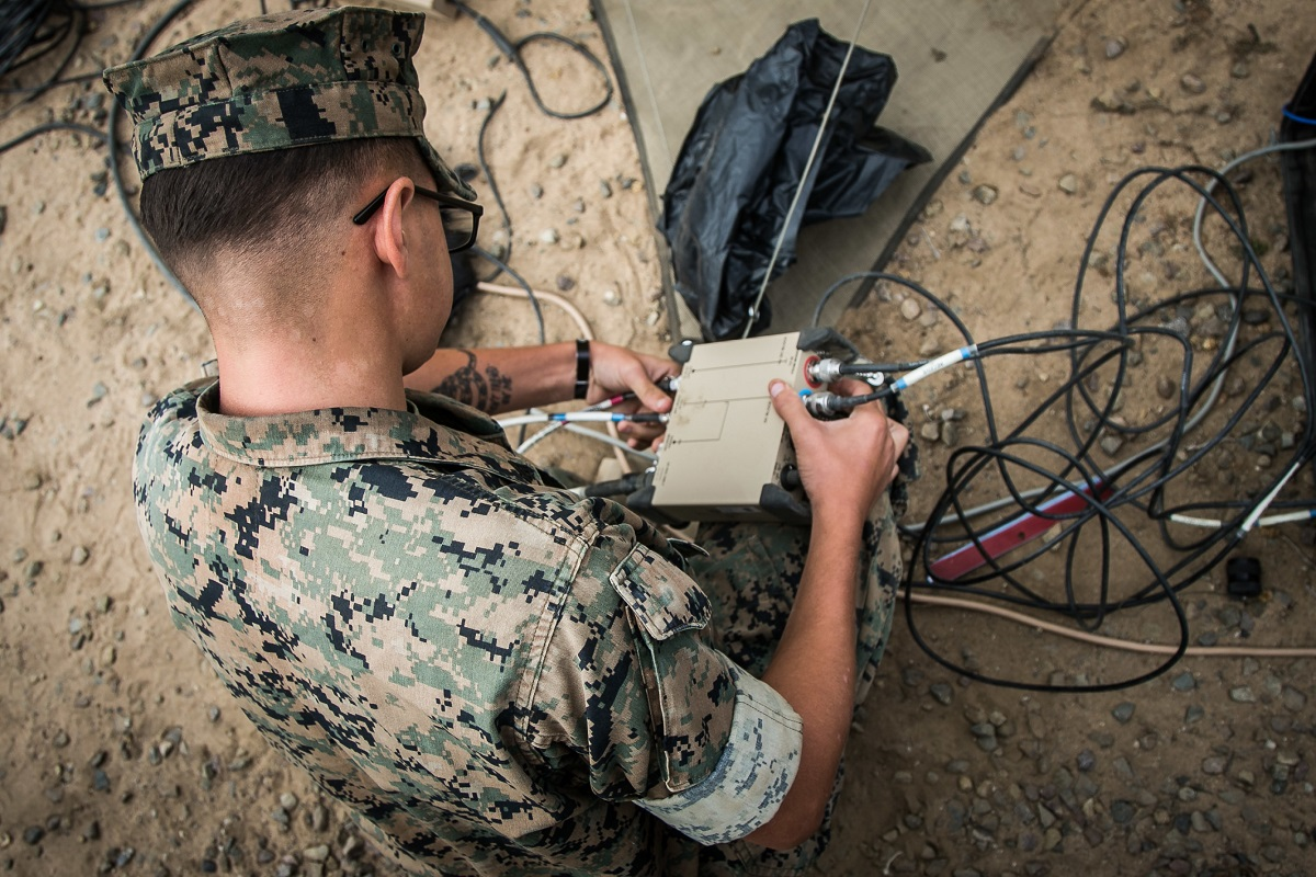 Cpl. Tyler Gustis, a satellite communication operator adjusts a ground antenna transmit and receiver satellite transformer during a command post exercise. (Cpl. Jeremy Laboy/Marine Corps)