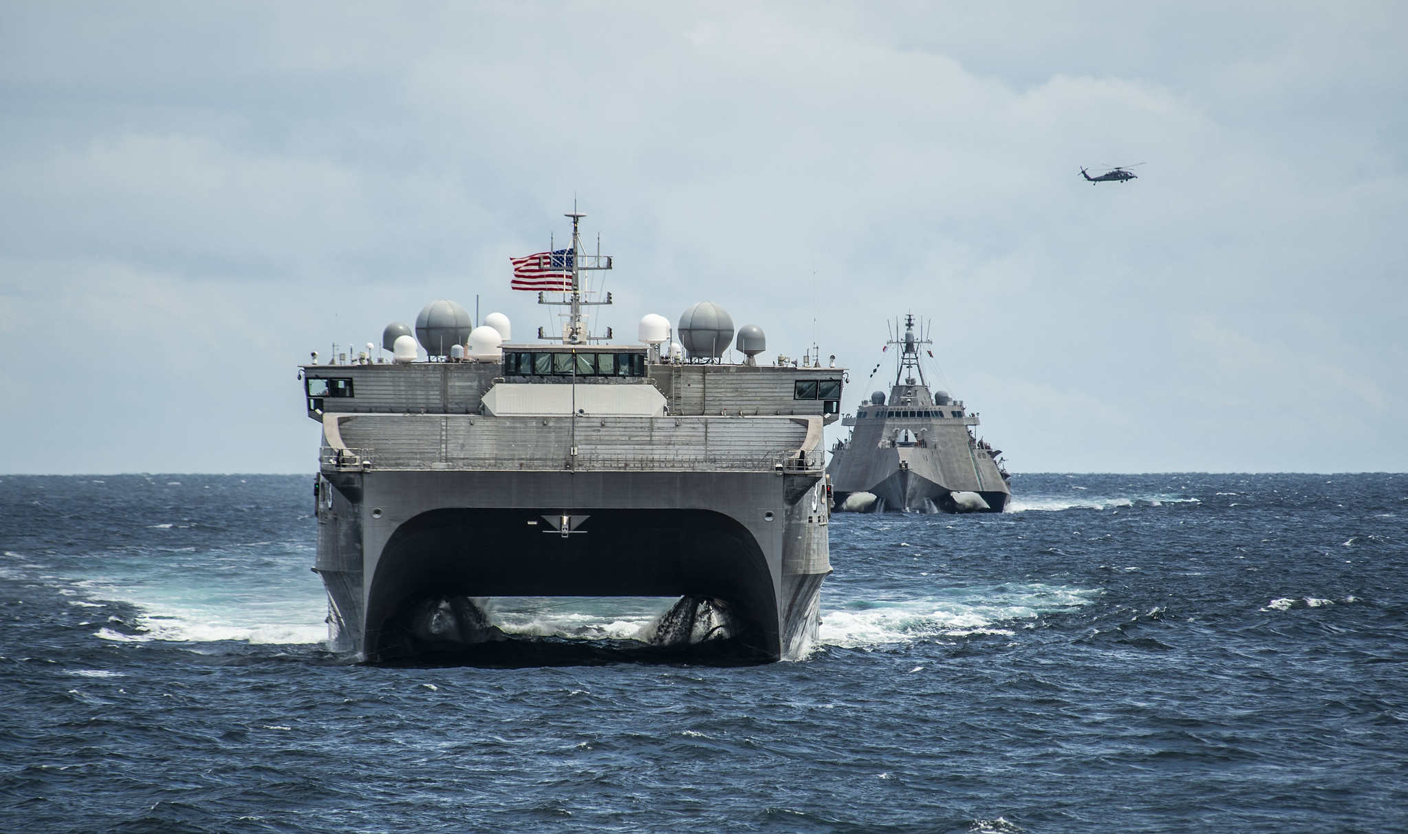 The Spearhead-class expeditionary fast transport ship USNS Millinocket (T-EPF 3), the Independence-variant littoral combat ship USS Montgomery (LCS 8) and an MH-60S Sea Hawk helicopter assigned to the Wildcards of Helicopter Sea Combat Squadron (HSC) 23 assemble in formation Oct. 29, 2019, for a photo exercise in support of Cooperation Afloat Readiness and Training (CARAT) Brunei. (Mass Communication Specialist 2nd Class Christopher A. Veloicaza/Navy)