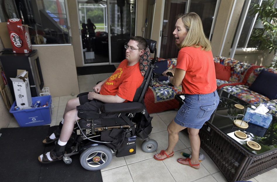 Chris Ott, right, helps maneuver her son, former Marine John Thomas Doody, around their family house in September 2013. J.T., left, as everyone calls him, was shot while serving in Fallujah, Iraq., and subsequently suffered an infection and a series of strokes that left him in a coma and relying on a ventilator to survive. (Chris O'Meara/AP)