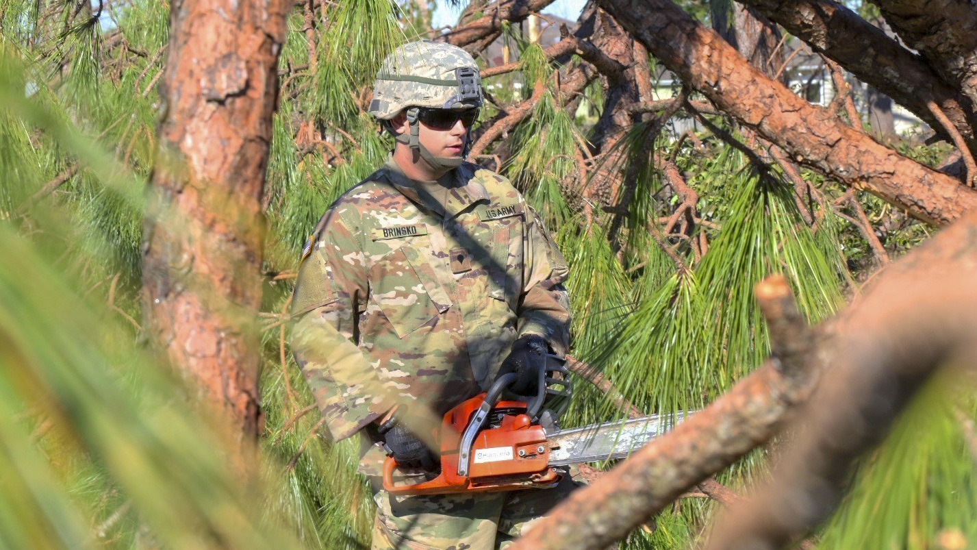 Florida National Guard Spc. Thomas Brinsko, with the 753rd Brigade Engineer Battalion, Alpha Co., from Tallahassee, Florida, cuts and removes tree branches from the roadways after the strike of Hurricane Michael, Oct. 13, 2018, in Panama City, Florida. (Pfc. Arcadia Jackson/National Guard)