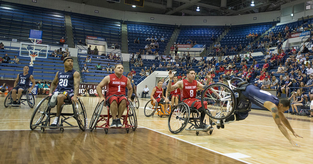 Navy veteran Chief Petty Officer Javier Santiago is upended as Navy defeats Marine Corps to win the wheelchair basketball bronze medal during the 2018 DoD Warrior Games at the U.S. Air Force Academy in Colorado Springs on June 9, 2018. (Roger L. Wollenberg/DoD)