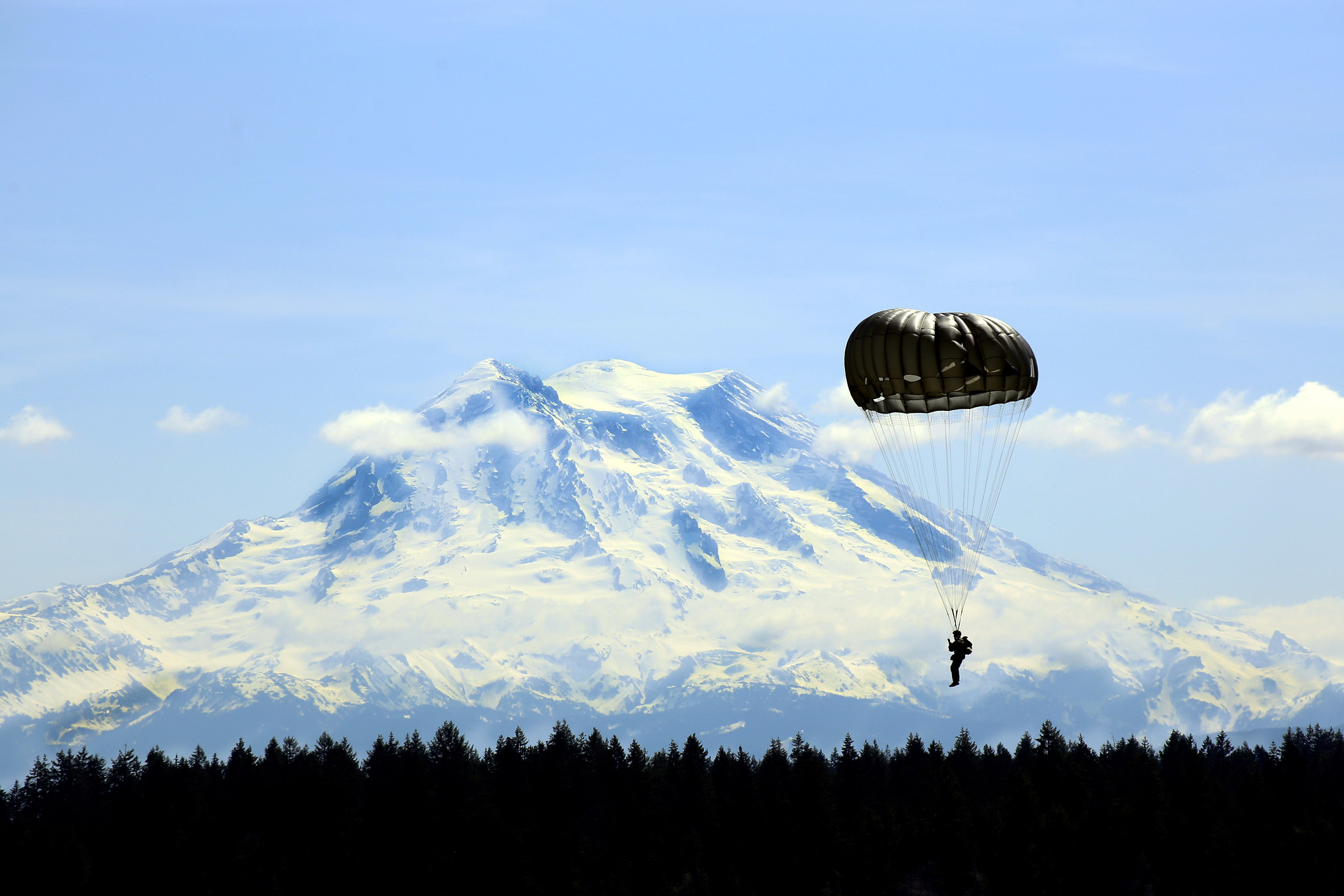 A Guardsman with Alpha Company, 1st Battalion, 19th Special Forces Group parachute past Mount Rainier on Joint Base Lewis-McChord on May 5, 2019. (Joseph Siemandel/National Guard)