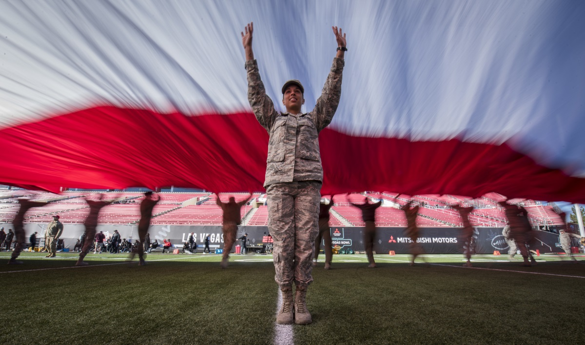 Airman 1st Class Ashley Libby, a 99th Medical Operations Squadron aerospace medical technician at Nellis Air Force Base, Nev., raises her arms to keep the American flag off the ground during the 2018 Las Vegas Bowl opening ceremony at Sam Boyd Stadium in Las Vegas, Dec. 15, 2018. The half-ton flag required more than 200 airmen to carry it. (Senior Airman Andrew D. Sarver/Air Force)
