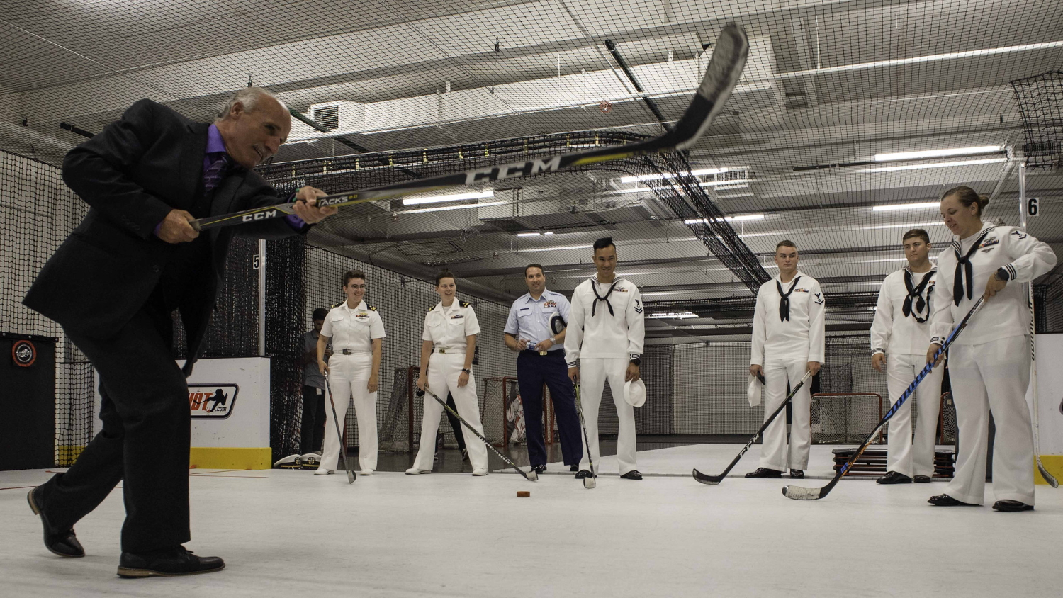 Daryl Evans, LA Kings alumni and commentator, teaches sailors assigned to the guided missile-destroyer USS Spruance (DDG 111) how to shoot a hockey puck Aug. 29, 2019, while touring Toyota Sports Center during Los Angeles Fleet Week. (Mass Communication Specialist 3rd Class Hector Carrera/Navy)