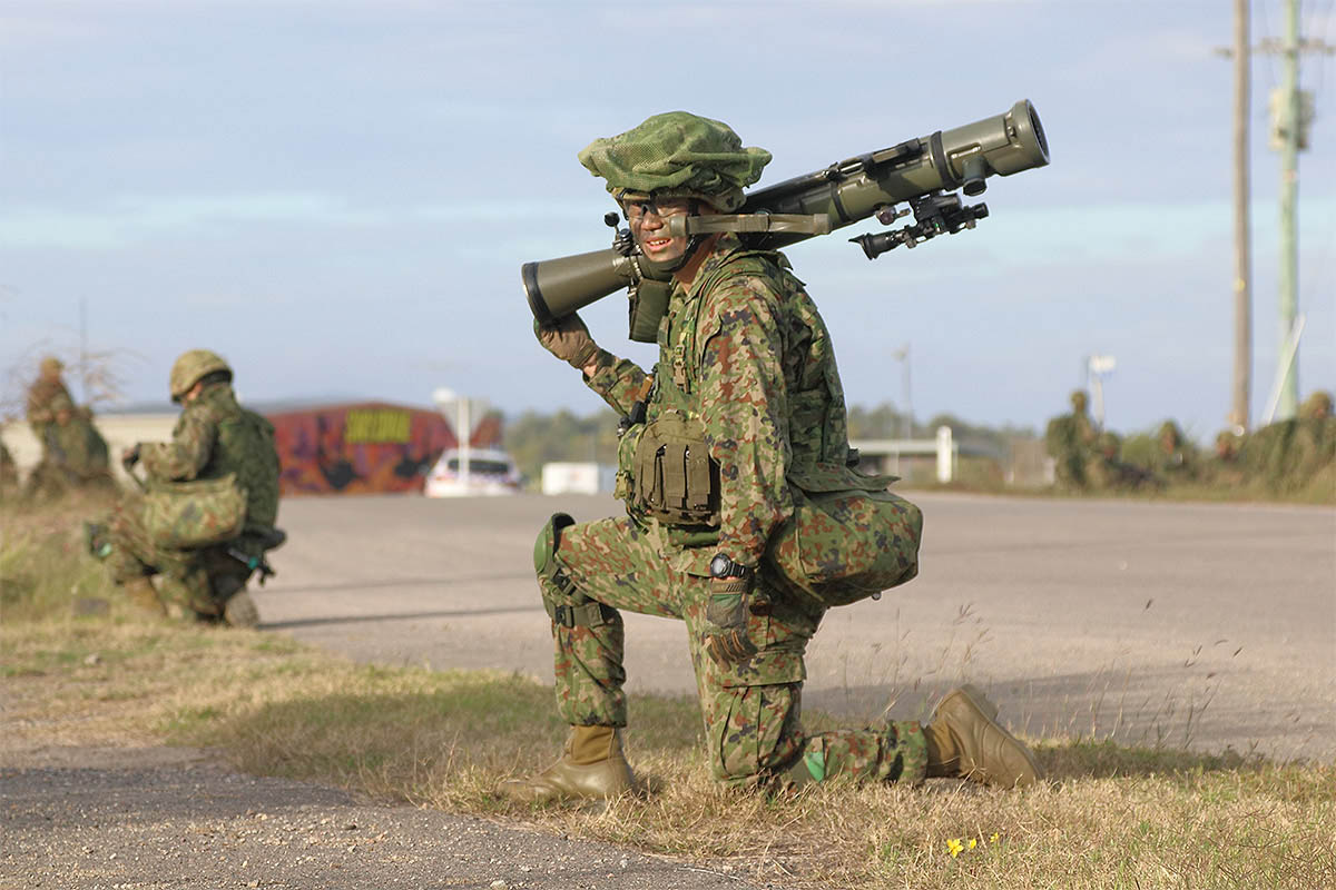 A Japanese recoilless rifle operator waits outside Bowen Airport, Australia, for orders to move out toward an objective during a helicopter assault drill. (Mike Yeo/Staff)