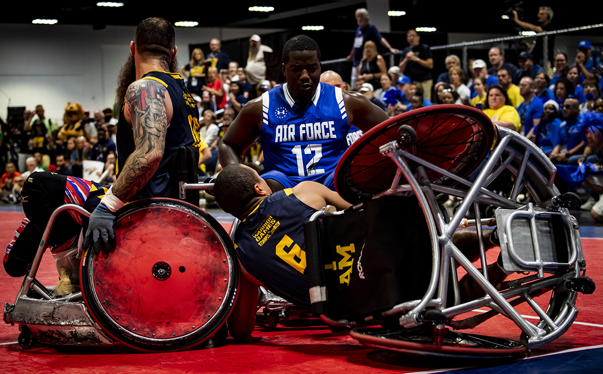 Air Force Senior Airman DeMarcus Garrett, Team Air Force athlete, powers through Team Navy defenders during the Department of Defense Warrior Games wheelchair rugby finals in Tampa, Fla., June 28, 2019. (Staff Sgt. James R. Crow/Air Force)