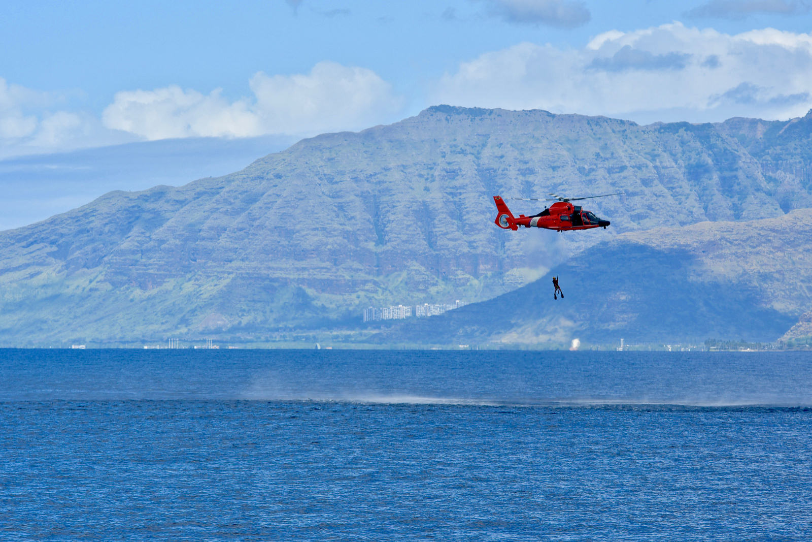 The crew of an Air Station Barbers Point MH-65 Dolphin helicopter raises their rescue swimmer during a search-and-rescue exercise in the vicinity offshore from Ko'olina to Kahe Point, Oahu, on Nov. 29, 2018. (Lt. j.g. Joshua Martin/Coast Guard)