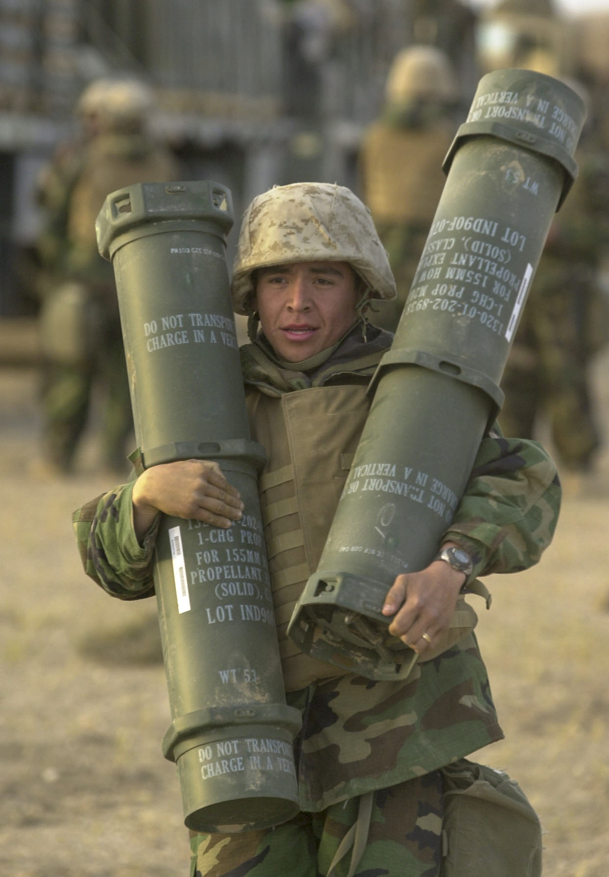Lance Cpl. Steven Lopez, 19, with Battery M, 3rd Battalion, 11th Marine Regiment from Los Angeles, CA carries two charges for a 155mm howitzer during a ammunition resupply at an artillery position in southern Iraq on March 22, 2003. 03/22/2003 ( Jud McCrehin/Marine Corps Times)
