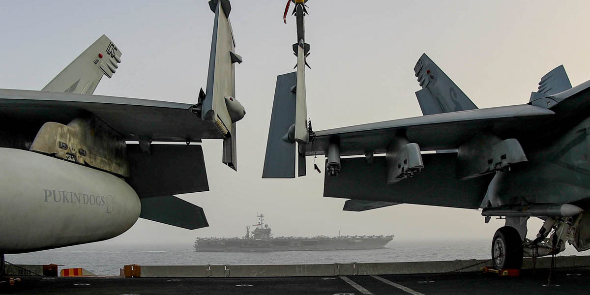 The aircraft carrier John C. Stennis is framed under the wings of a pair of F/A-18 Hornets on the aircraft carrier Lincoln's flight deck(Mass Communication Specialist 2nd Class Jessica Paulauskas/Navy)