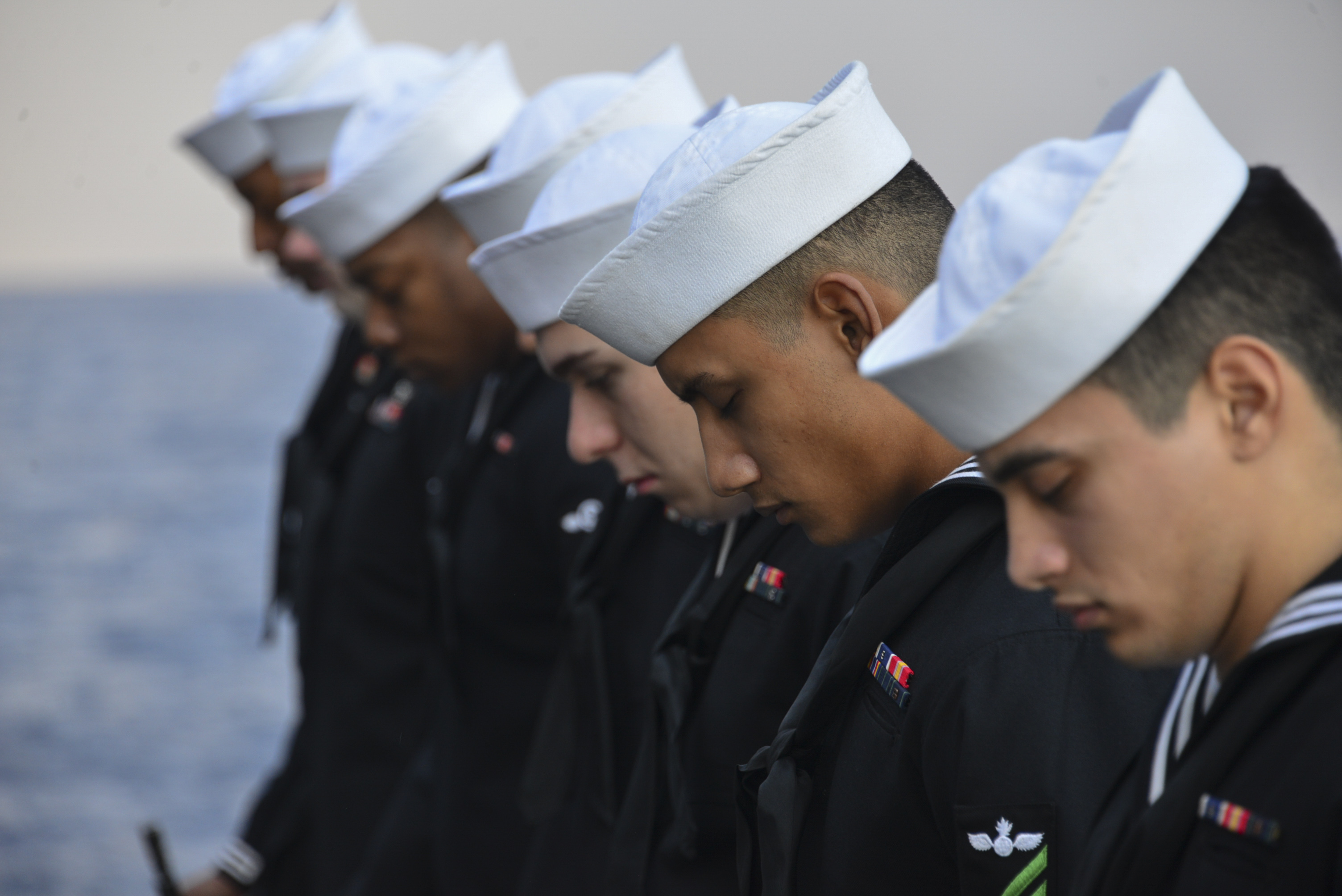 Sailors part of the rifle detail bow their heads in prayer during a Burial at Sea ceremony held on the starboard aircraft elevator of the amphibious assault ship USS Iwo Jima. U.S. Navy photo by Hunter S. Harwell