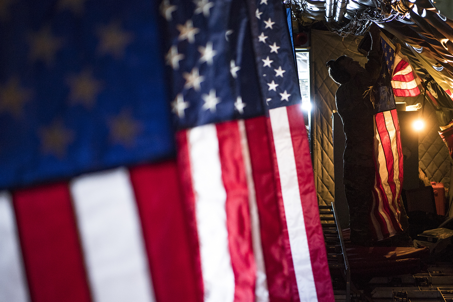 A 28th Expeditionary Air Refueling Squadron pilot hangs the American flag inside a KC-135 Stratotanker at Al Udeid Air Base, Qatar, Sept. 24, 2019. (Master Sgt. Russ Scalf/Air Force)