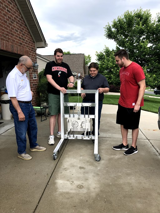 Vietnam veteran Mike Donnelly with University of Cincinnati engineering students, who built a device to help him lift his scooter carrier to his car hitch. The project was sponsored by the nonprofit Quality of Life Plus. Photo courtesy of Quality of Life Plus
