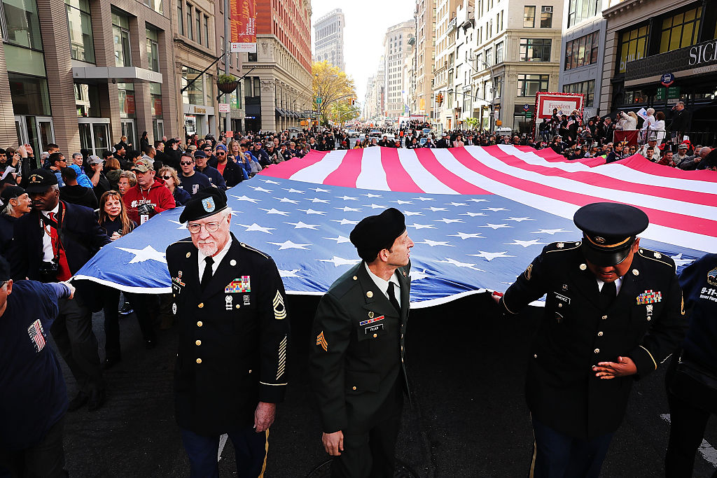 Veterans and others carry a large American flag while marching in the nation's largest Veterans Day Parade in New York City on Nov. 11, 2016. (Spencer Platt/Getty Images)