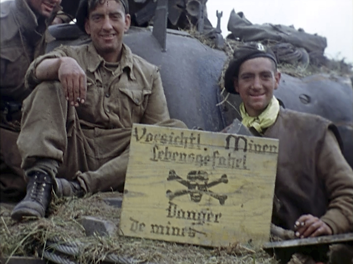 Soldiers sit on a tank holding a sign about a mine field during World War II in France on June 6, 1944. Seventy-five years later, surprising color images of the D-Day invasion and aftermath bring an immediacy to wartime memories. They were filmed by Hollywood director George Stevens and rediscovered years after his death. (War Footage From the George Stevens Collection at the Library of Congress via AP)