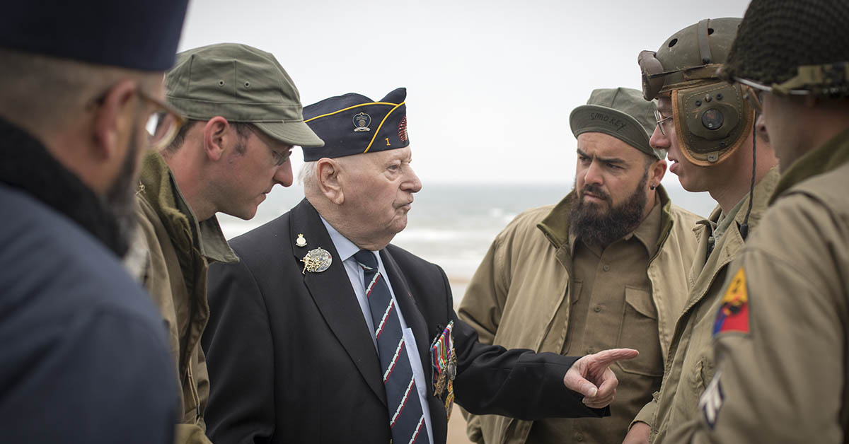 World War 2 re-enactors talk with Normandy veterans attending a wreath laying ceremony at the Tactical Air Force Memorial besides Omaha Beach at Vierville-sur-Mer in Normandy on June 4, 2018 near Bayeux, France. As the 74th anniversary of the D-Day approaches, some of the handful of surviving Normandy Veterans are making their way to France to commemorate the landings, which saw 156,000 troops from the allied countries including the United Kingdom, the United States and France join forces to launch an audacious attack on the beaches of Normandy which helped lead to the eventual defeat of Nazi Germany. (Matt Cardy/Getty Images)