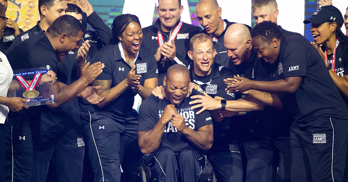 Army SPC Brent Garlic is congratulated after receiving the U.S. Army Heart of the Team award during the Closing Ceremony at the 2018 Department of Defense Warrior Games June 9, 2018 at the Air Force Academy in Colorado Springs, Colo. (Mark Reis/DoD)