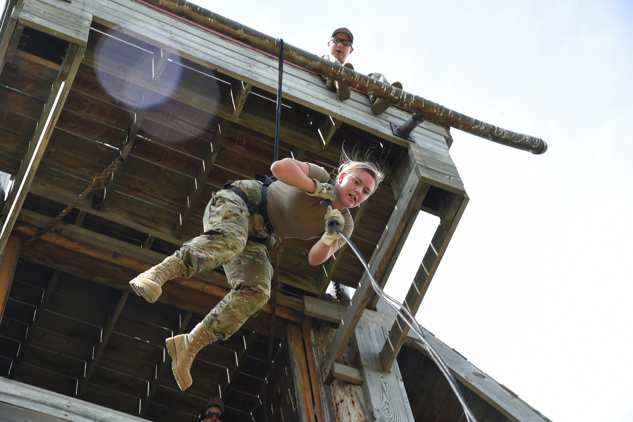 Airman 1st Class Maggie Hebert lowers herself on a rope using an