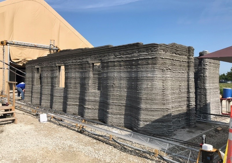 A larg concrete 3D printer constructs a 500-square-foot barracks hut at the U.S. Army Engineer Research and Development Center in mid-August in Champaign, Ill.. (Courtesy of the U.S. Marine Corps)