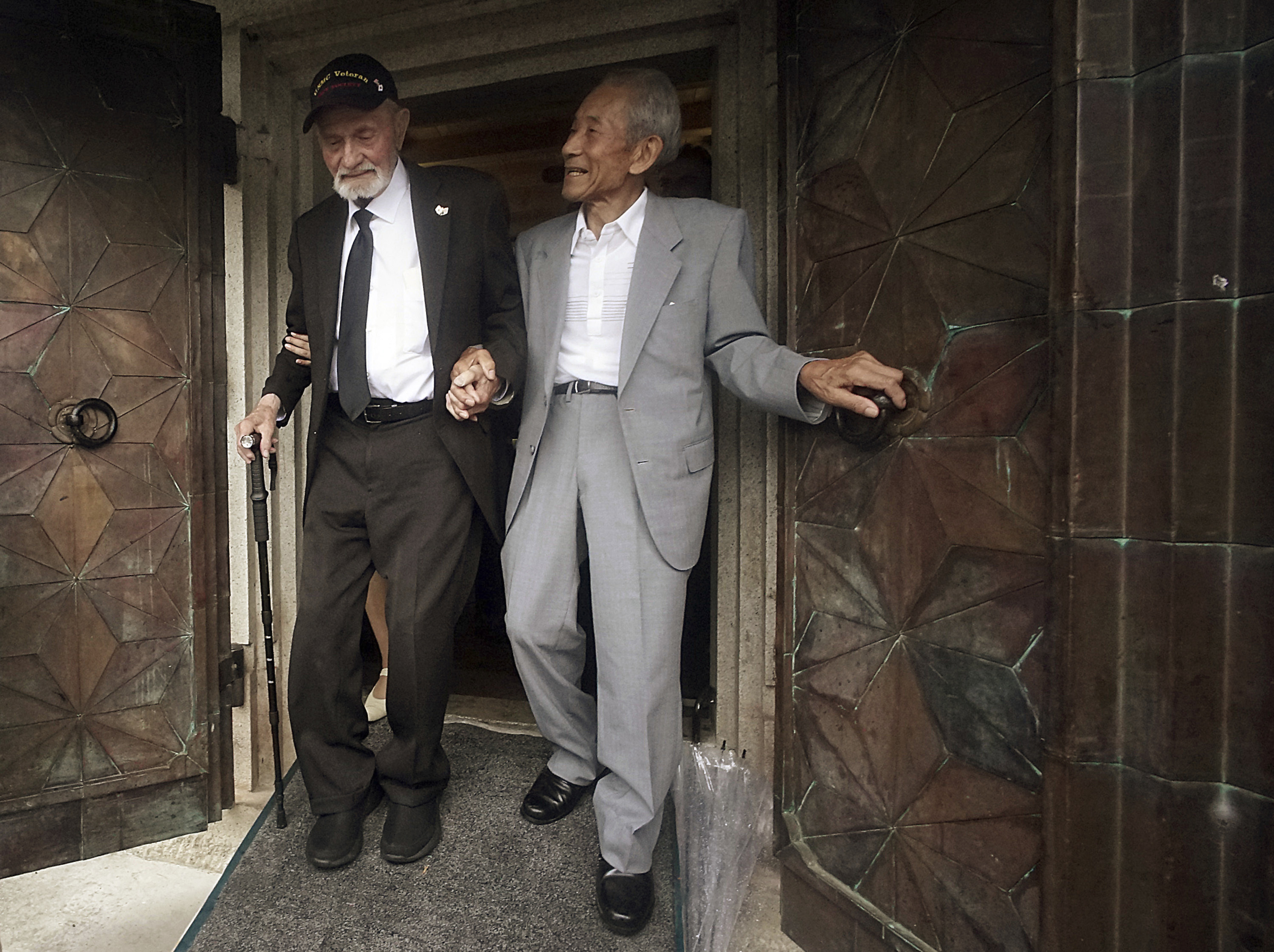 Tatsuya Yasue, right, and WWII veteran Marvin Strombo walk together out from a village's war memorial prior to a ceremony in Higashishirakawa, in central Japan's Gifu prefecture Tuesday, Aug. 15, 2017. (Eugene Hoshiko/AP)