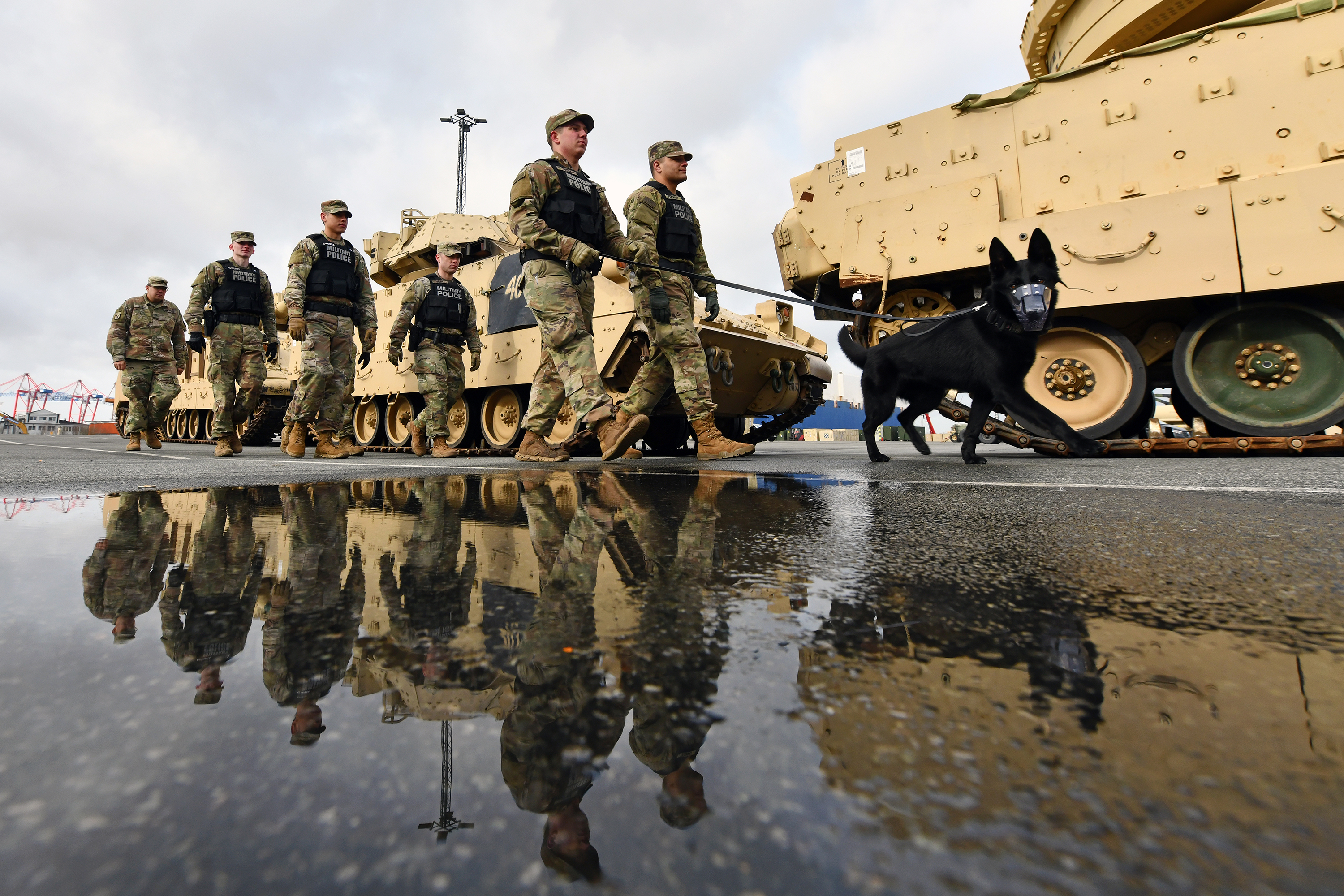 U.S. soldiers assigned to 527th Military Police Company, 615th Military Police Company and 100th Military Working Dog Detachment conduct security rounds at Bremerhaven Port, Bremerhaven, Germany, on Feb. 21, 2020. (Jason Johnston/Army)