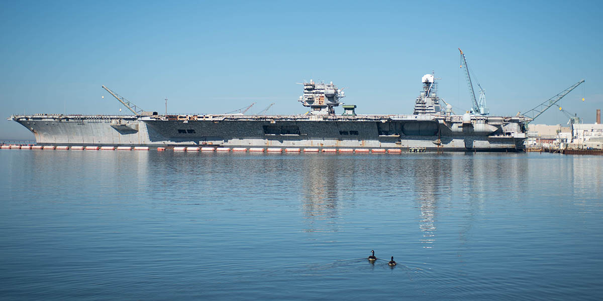 The island of the next-gen carrier Gerald R. Ford (r) peaks up over the rusting hulk of the aircraft carrier Enterprise. (Mark D. Faram/Staff)