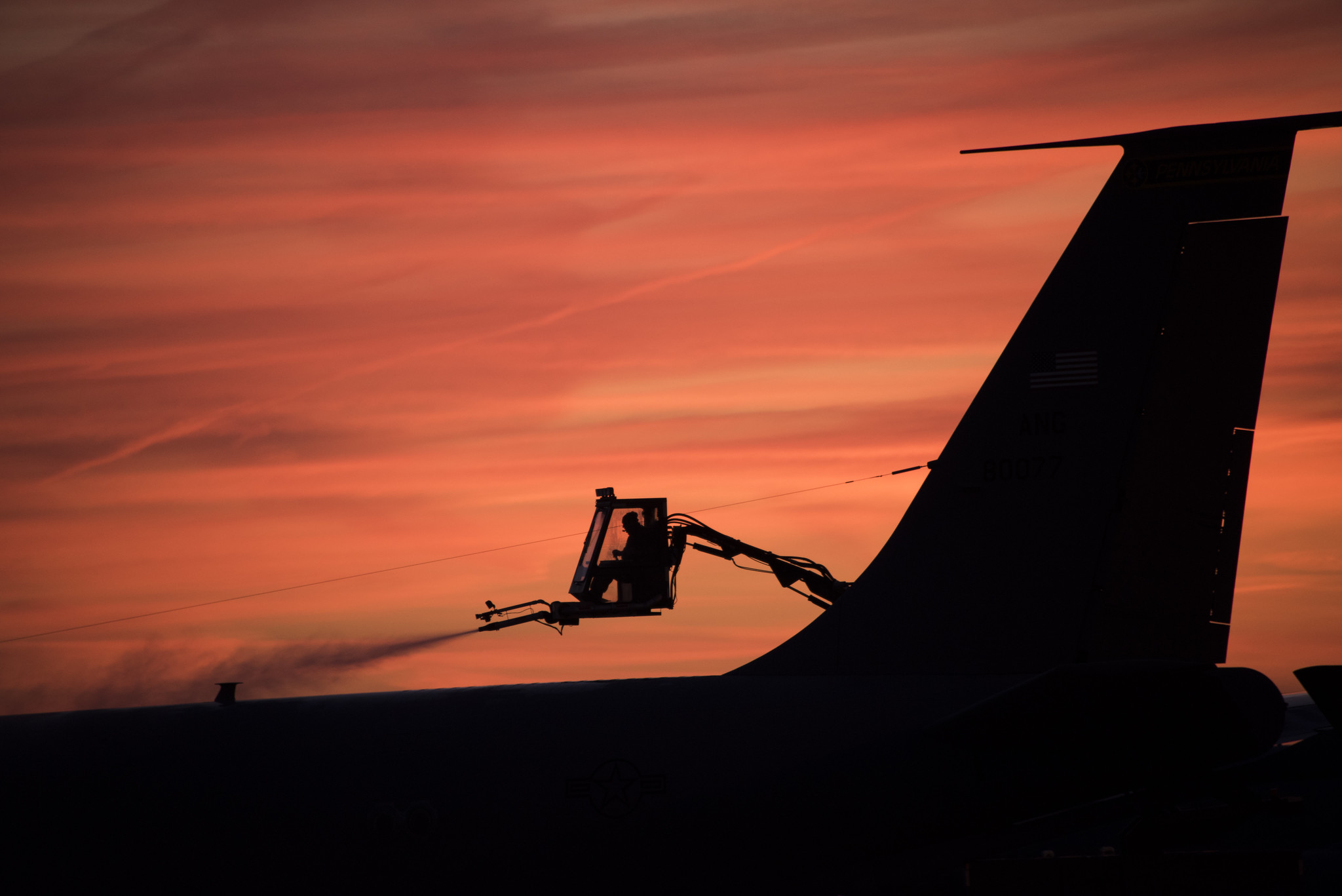 Tech. Sgt. Joshua Nordeen, a Pennsylvania Air National Guardsman, deices an aircraft early in the morning as the sun rises in Pittsburgh, Pa., on Dec. 12, 2019. (Staff Sgt. Bryan Hoover/Pennsylvania Air National Guard)