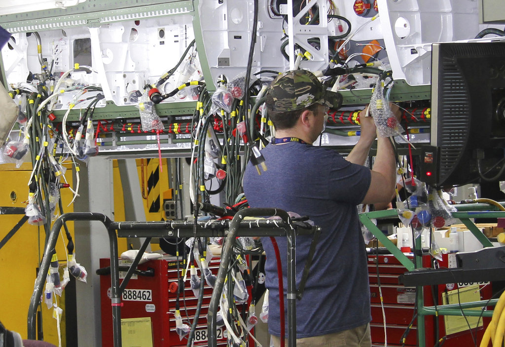 Workers perform hydraulics testing on a new F/A-18 at Boeing's fighter aircraft production line in St. Louis, Mo. (Ted Shaffrey/AP)