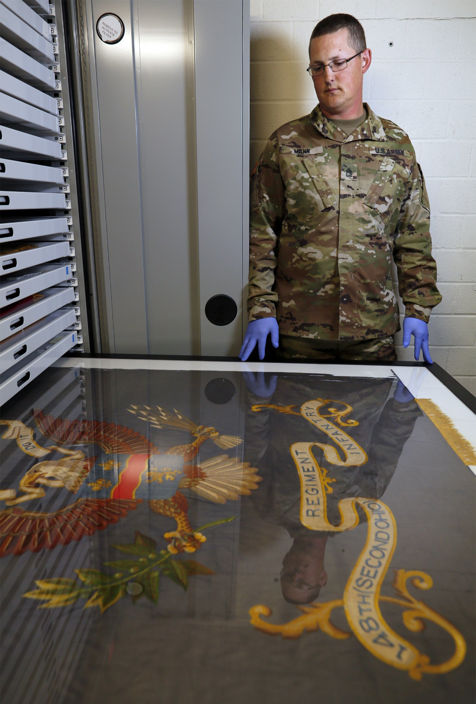 In this July 17, 2018, photo, Sgt. 1st Class Josh Mann, the Ohio Army National Guard historian, looks at a Civil War battle flag from the 148th Infantry Regiment inside the Beightler Armory in Columbus, Ohio. The Ohio National Guard is celebrating its 230 years of service. (Adam Cairns/The Columbus Dispatch via AP)
