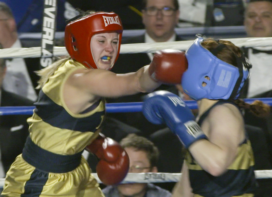 Mikayla Lint (in gold) hits Darcy Stack, right, (in blue) during the 139 lb weight class bout at the United States Naval Academy's 77th Brigade Boxing Championships held on Feb. 23, 2018. (Alan Lessig/Staff)