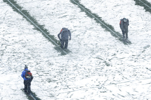 Members of the grounds crew clear lines on the field as snow falls ahead of Saturday's game in Philadelphia. (Matt Rourke/AP)