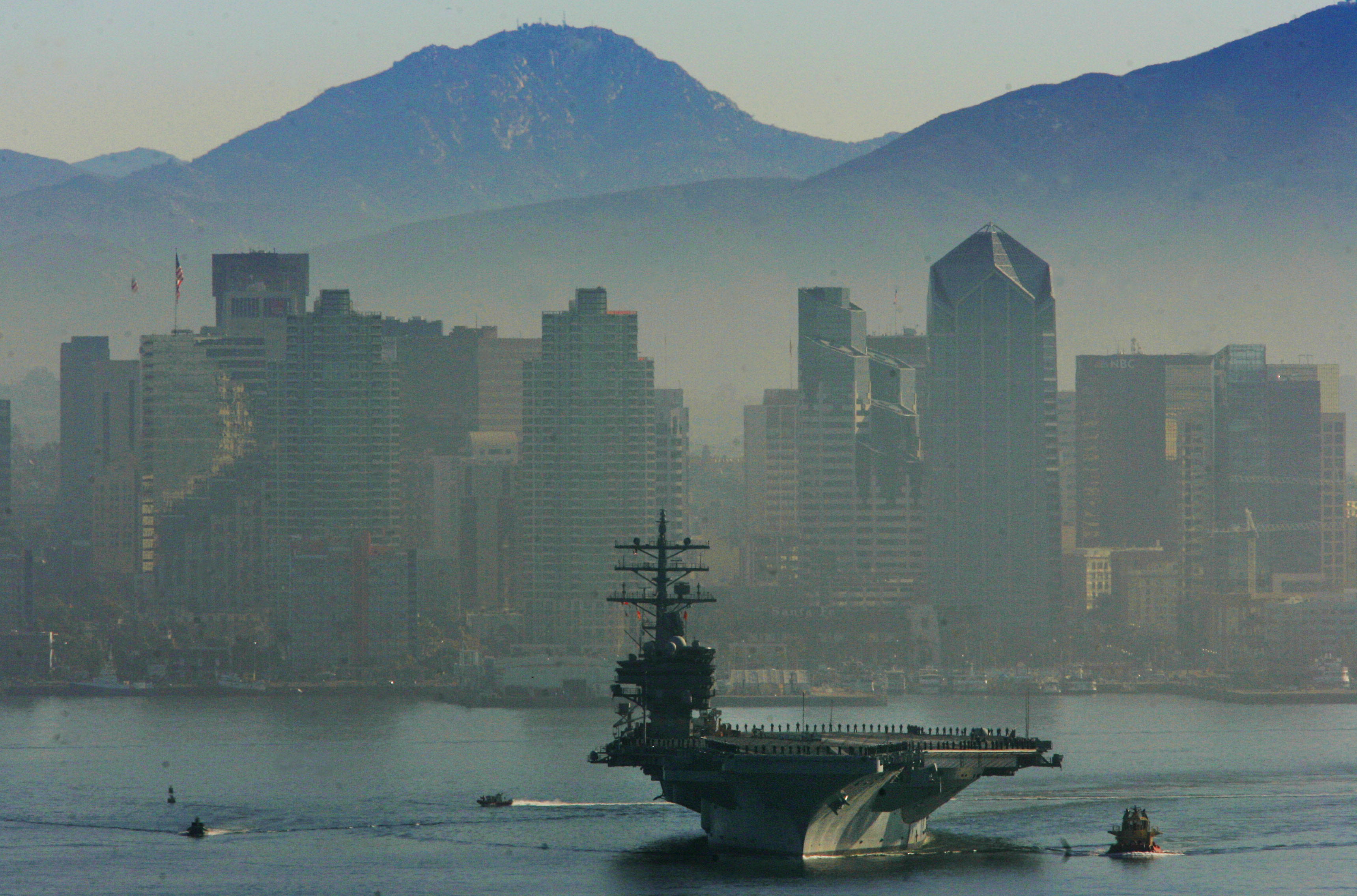 The USS Ronald Reagan heads out to sea with the San Diego skyline in the background Jan. 4, 2006, at Naval Air Station Coronado, California. (Sandy Huffaker/Getty Images)