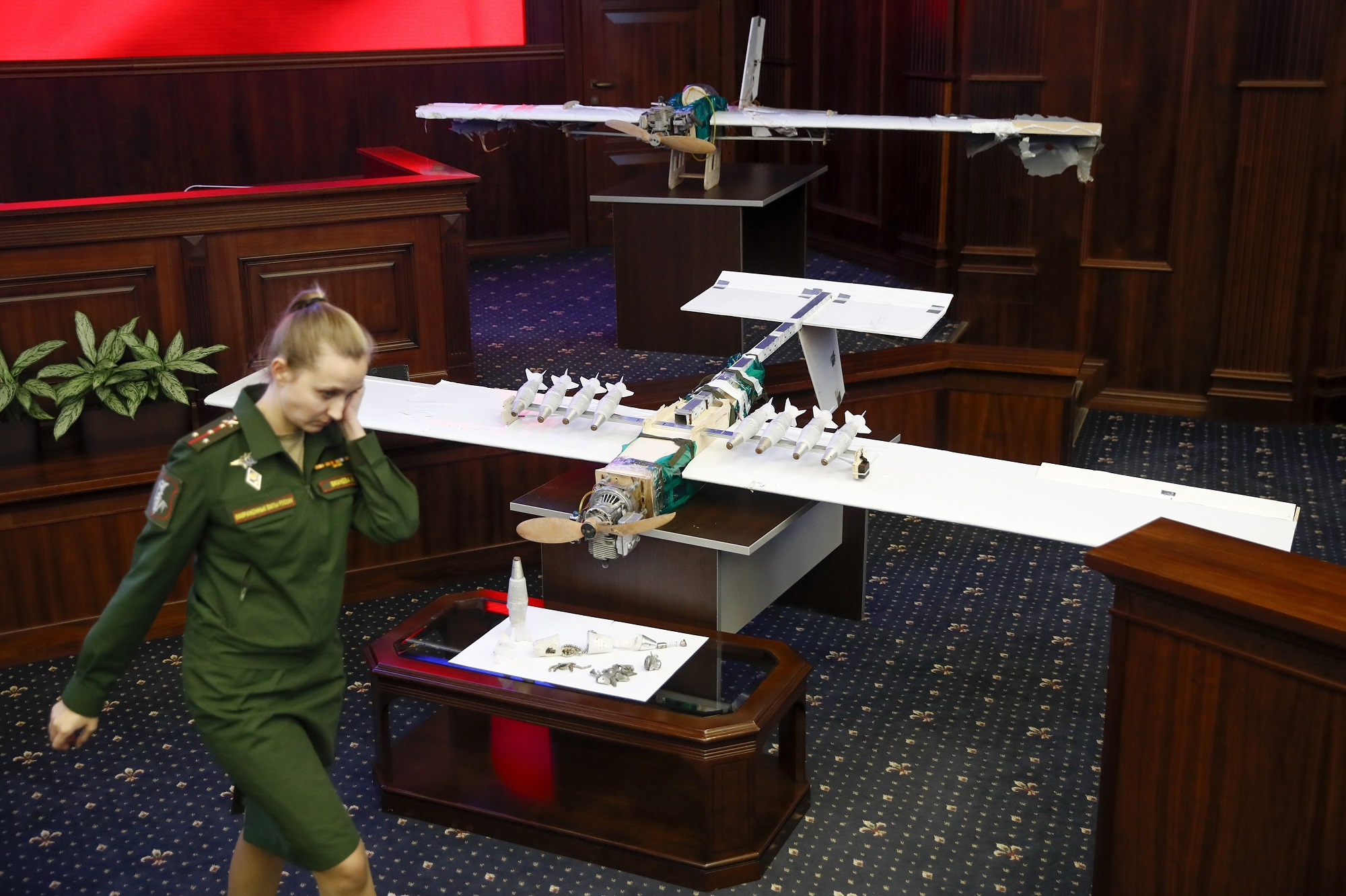 A Russian officer walks next to drones that allegedly attacked a Russian air base in Syria and were captured by the Russian military. They were displayed at a briefing in the Russian Defence Ministry in Moscow, Russia, on Jan. 11, 2018. (Pavel Golovkin/AP)