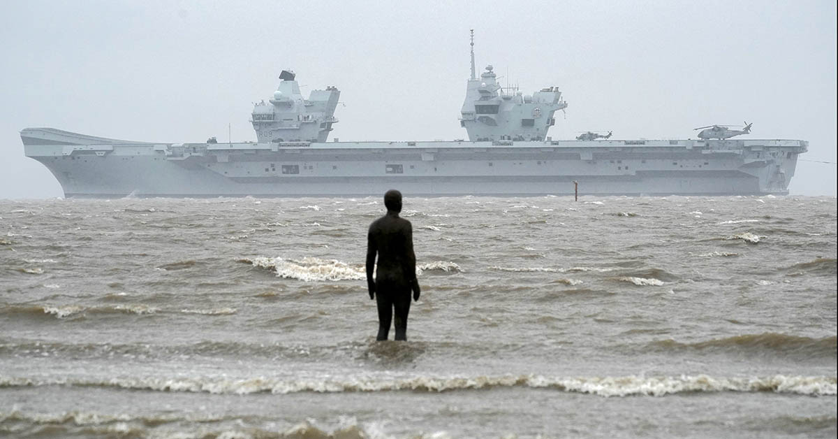 LIVERPOOL, ENGLAND - FEBRUARY 28: Royal Navy aircraft carrier, HMS Prince of Wales, sails past the statues of 'Another Place' as it arrives in Liverpool on February 28, 2020 in Liverpool, England. The Royal Navy's newest aircraft carrier completed its journey from Portsmouth Naval Base to Liverpool in heavy rain and high winds. (Photo by Christopher Furlong/Getty Images)