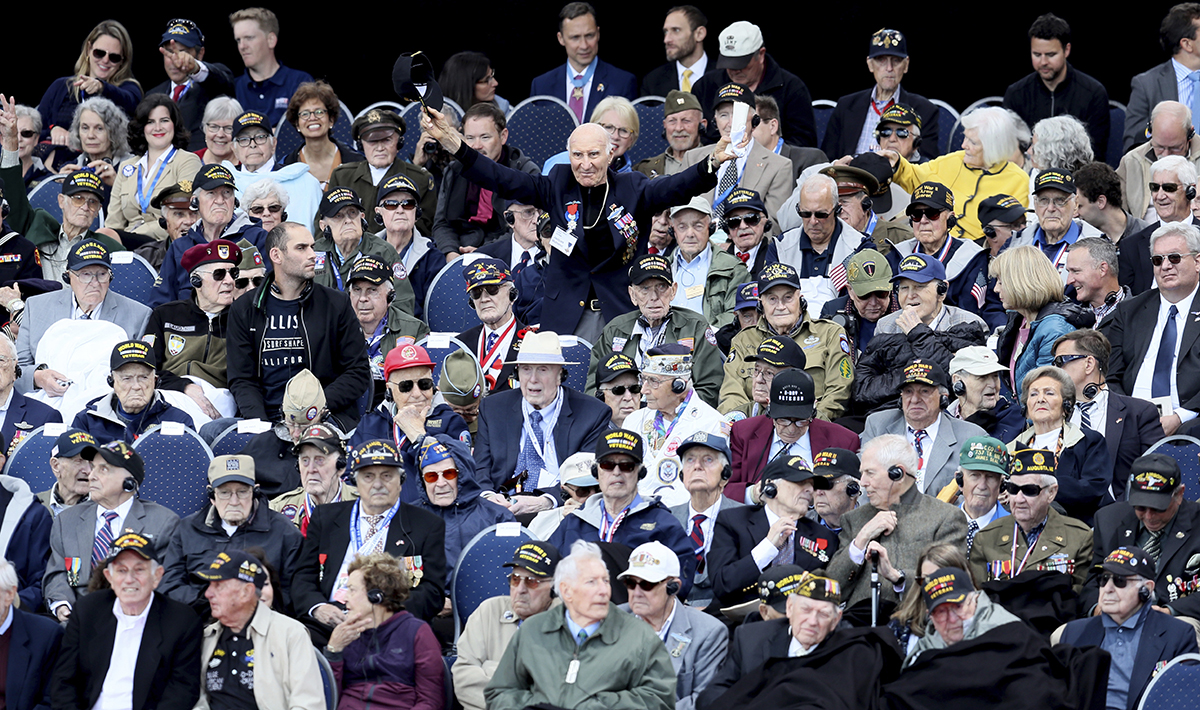 U.S. World War II veteran Jacques Michienzi, center, stands up among other veterans during a ceremony to mark the 75th anniversary of D-Day at the Normandy American Cemetery in Colleville-sur-Mer, Normandy, France, Thursday, June 6, 2019. World leaders are gathered Thursday in France to mark the 75th anniversary of the D-Day landings. (David Vincent/AP)