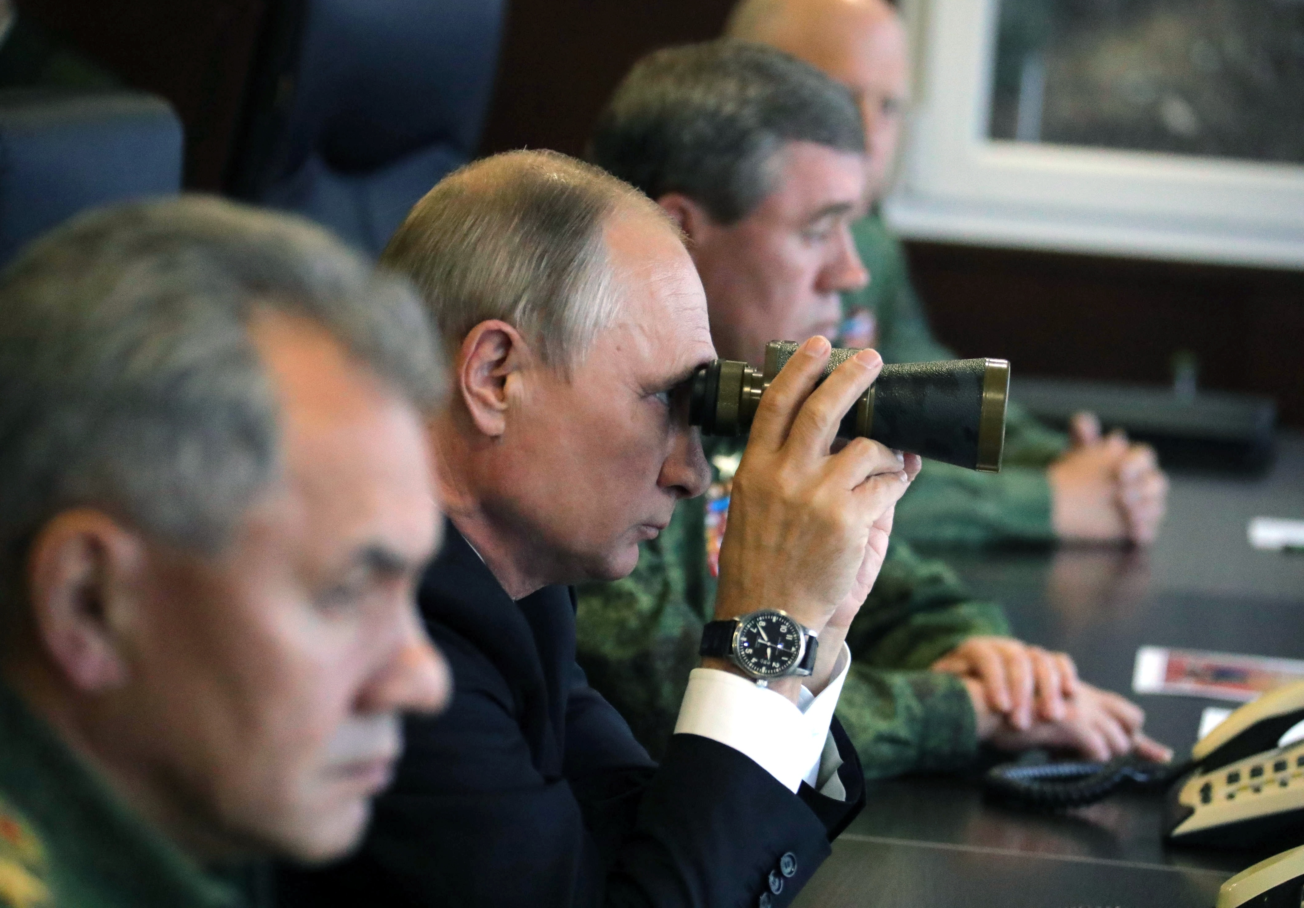 Russian President Vladimir Putin, center, Defence Minister Sergei Shoigu, left, and Chief of the General Staff of the Russian Armed Forces Valery Gerasimov, right, watch a military exercise at a training ground at the Luzhsky Range, near St. Petersburg, Russia, on Sept. 18, 2017. (Mikhail Klimentyev/Sputnik/Kremlin Pool Photo via AP)