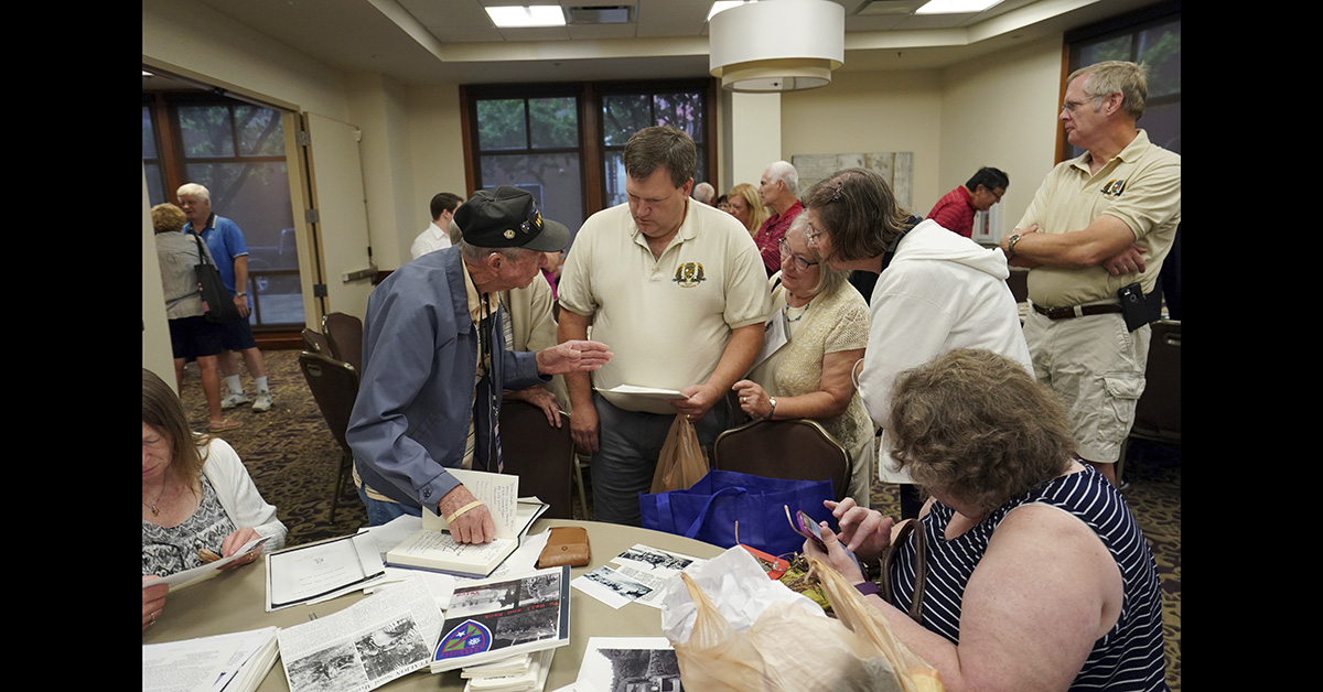 Lester Hollenback, of Deltona, Fla., left, a surviving member of the famed WWII Army unit Merrill's Marauders, talks with visitors as they look over memorabilia, during a gathering of remaining members, family and history buffs, in New Orleans, Tuesday, Aug. 28, 2018. (Gerald Herbert/AP)