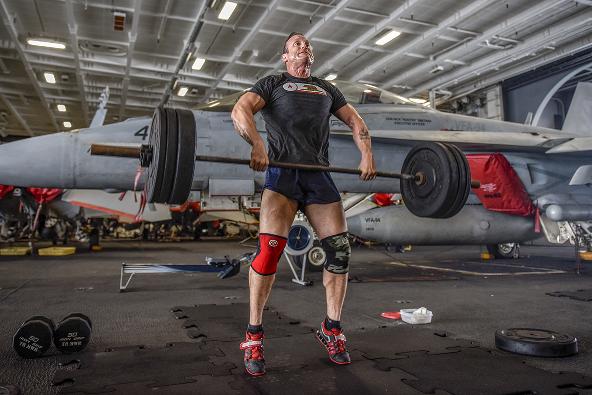 Lt. Joshua Johnson lifts weights in the hangar bay of the aircraft carrier USS Theodore Roosevelt (CVN 71). Theodore Roosevelt and its carrier strike group are deployed to the U.S. 5th Fleet area of operations in support of maritime security operations to reassure allies and partners and preserve the freedom of navigation and the free flow of commerce in the region. (MC3 Alex Perlman/Navy)