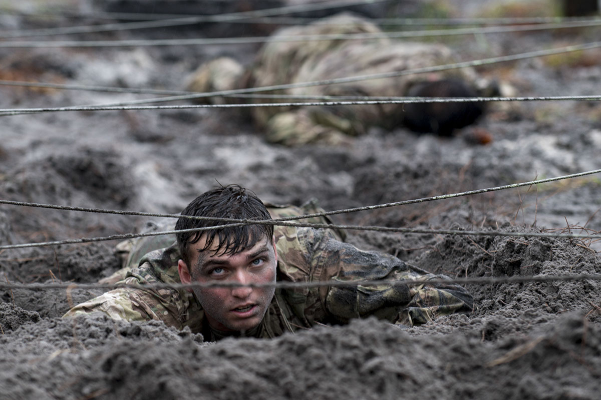 Airmen from the 820th Base Defense Group low crawl through an obstacle during an Army Air Assault readiness assessment, Dec. 7, 2017, at Camp Blanding, Fla. The AAA readiness assessment is designed to prepare Airmen for the Army Air Assault School curriculum as well as its physical and mental stressors. During AAA, U.S. troops are taught an array of skills associated with rotary-winged aircraft. These skills widen the 820th BDG's ability to swiftly deploy and defend. (Senior Airman Daniel Snider/Air Force)