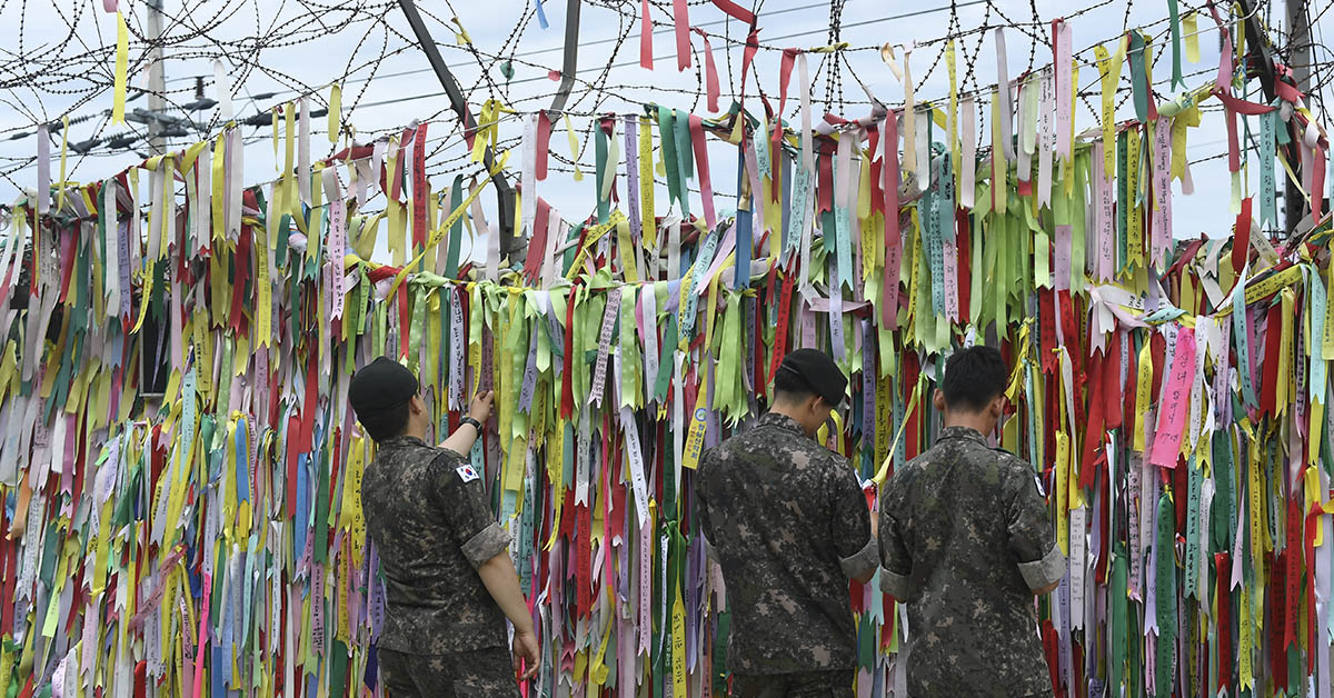 South Korean soldiers look at ribbons with inscriptions calling for peace and reunification displayed on a military fence at the Imjingak peace park near the Demilitarized Zone dividing the two Koreas in the border city of Paju on June 11, 2018. (Jung Yeon-Je/AFP via Getty Images)