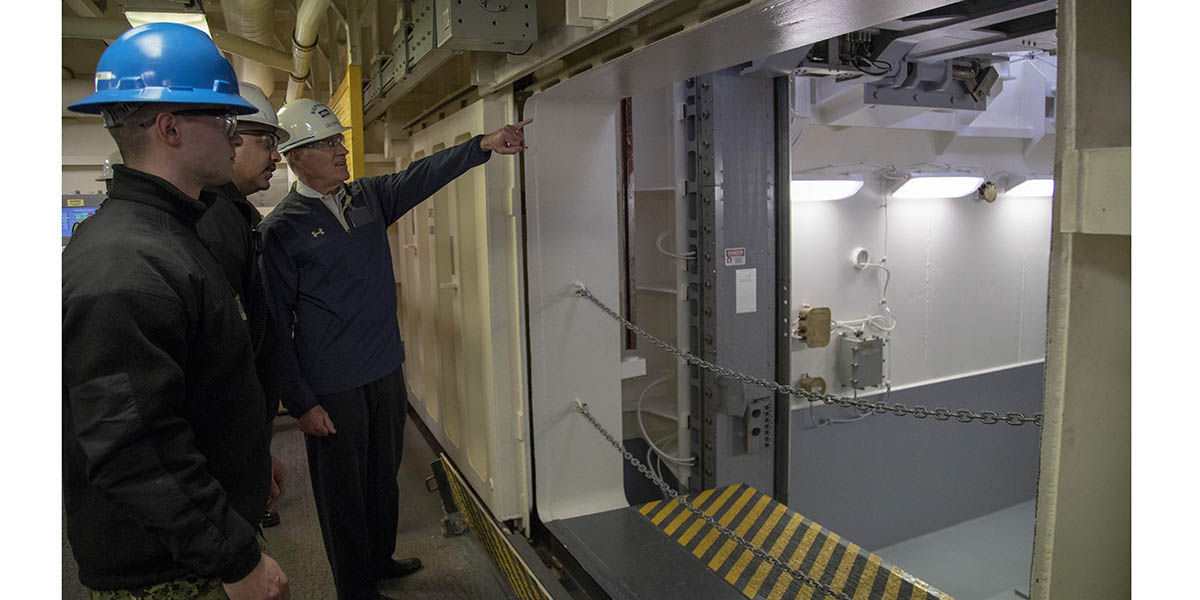 Secretary of the Navy Richard V. Spencer is briefed by Lt. Cmdr. Chabonnie Alexander, the aircraft carrier Gerald R. Ford's ordnance handling officer, on the Upper Stage 1 advanced weapons elevator during a tour of the Navy's newest aircraft carrier. (Mass Communication Specialist 2nd Class Kiana A. Raines)