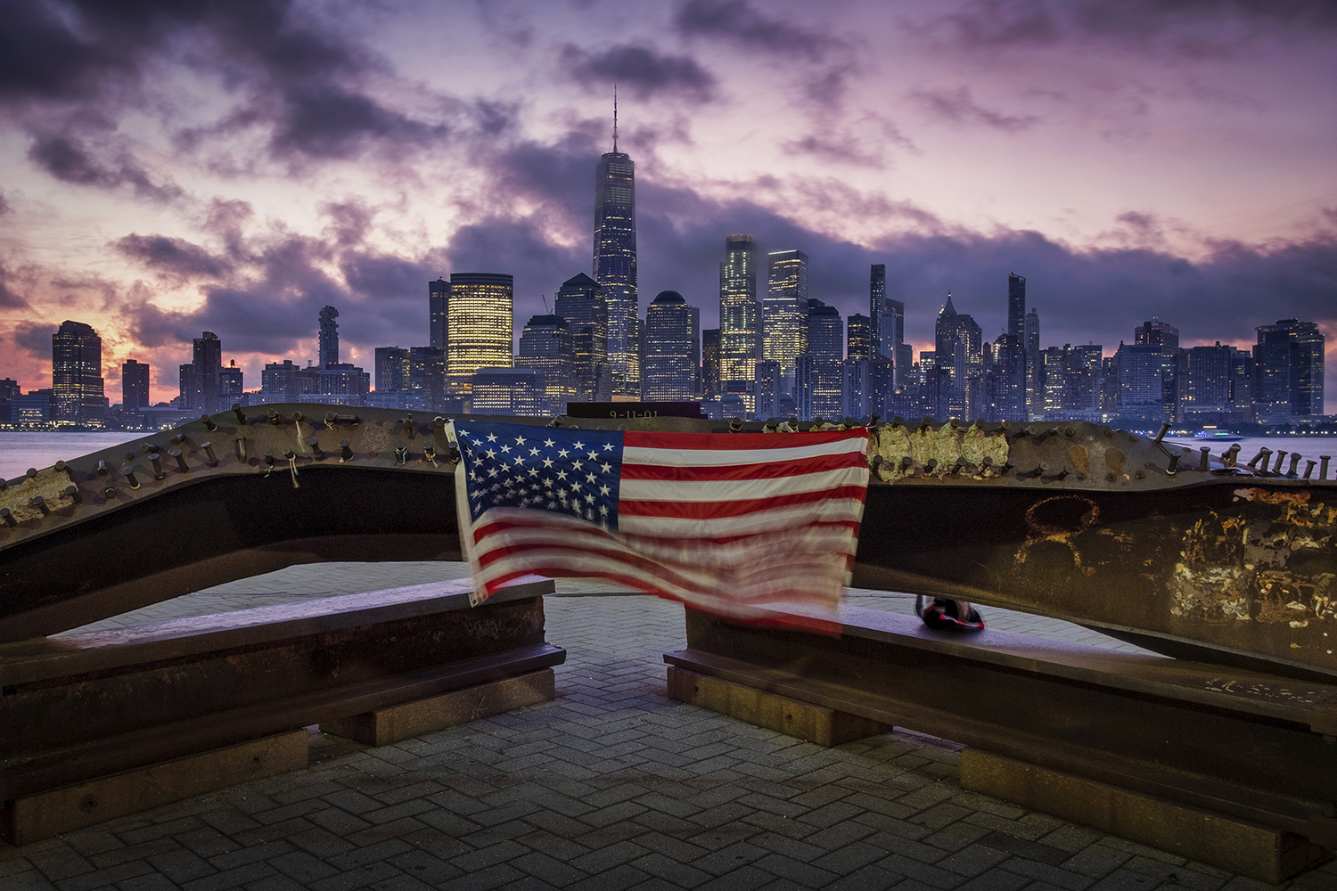 A U.S. flag hanging from a steel girder, damaged in the Sept. 11, 2001, attacks on the World Trade Center, blows in the breeze at a memorial in Jersey City, N.J., Sept. 11, 2019, as the sun rises behind One World Trade Center building and the re-developed area where the Twin Towers of World Trade Center once stood in New York City on the 18th anniversary of the attacks. (J. David Ake/AP)